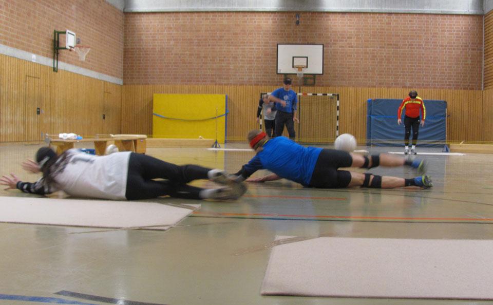Zwei Verteidiger werfen sich vor ihren Matten zu Boden. Der prallt vom Oberschenkel eines Spielers ab. Im Hintergrund das angreifende Team.