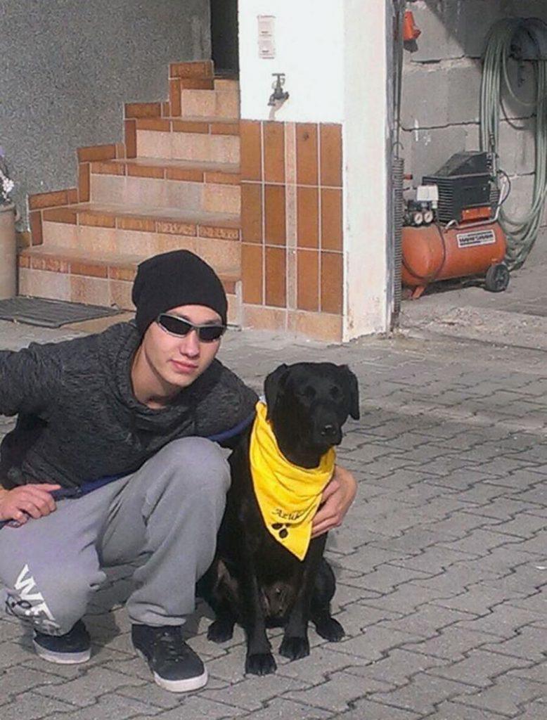 Marco trägt Mütze und Sonnenbrille. Er kniet mit seinem neuen, schwarzen Blindenhund in einer Einfahrt