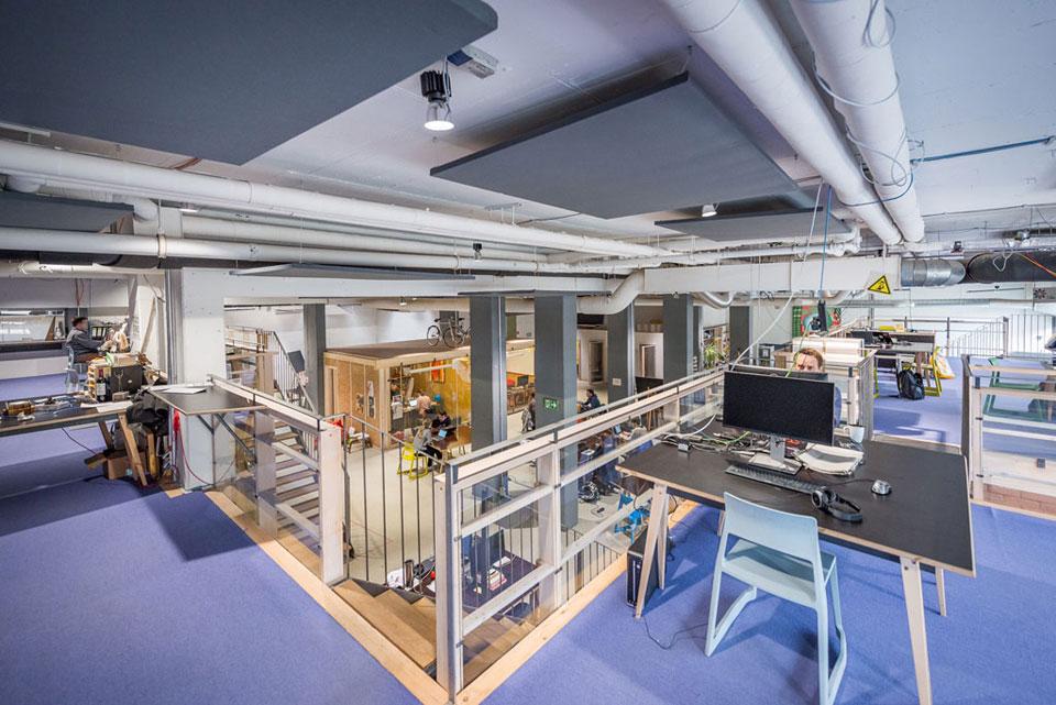 Blick im Impact Hub von der Galerie auf den geteilten Arbeitsraum. An der Decke verlaufen Rohre, einige Mitglieder sitzen hinter Computer-Monitoren und arbeiten