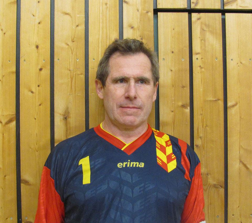 Hans Demmelhuber, braune Haare, blickt entschlossen in die Kamera. Erträgt ein schwarzes Trikot mit roten Ärmeln und einer gelben Nummer eins auf der rechten Brust.