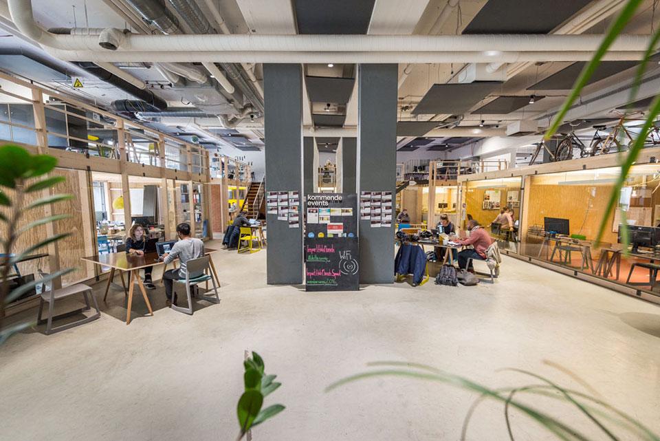 Der geteilte Arbeitsraum des Impact Hub. In der Mitte des Bildes stehen zwei Säulen mit Profilzetteln, dazwischen Kündigt eine Tafel kommende Events an. Links und rechts wird der Raum von den Holzwänden und Glasfronten der Büros eingerahmt.