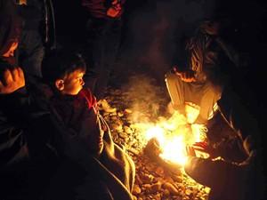 Flüchtlinge nachts am Lagerfeuer.