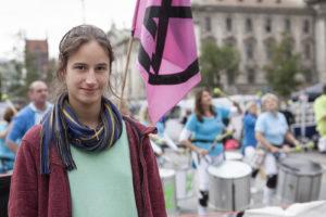 Portrait von Lisa Poettinger von Extinction Rebellion vor der Trommelgruppe Bateria Z