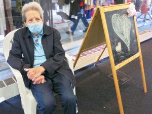 eine ältere Dame sitzt auf einem Stuhl und rastet