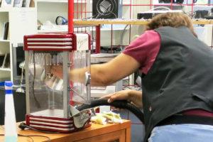 Eine Mitarbeiterin des diakonia-Kaufhauses saugt eine Popcornmaschine aus