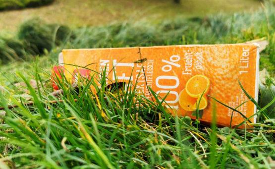 EIn Tetrapack Orangensaft liegt im Park