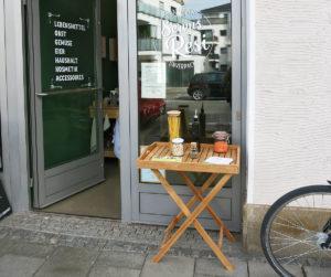 Vor der Eingangstüre steht ein Tisch auf dem allerlei Gläser mit Lebensmitteln drapiert sind