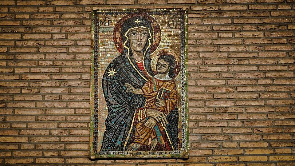 Das Bild zeigt ein Ikonen- Mosaik Gottesmutter Salus Populi Romani auf einer Ziegelwand.