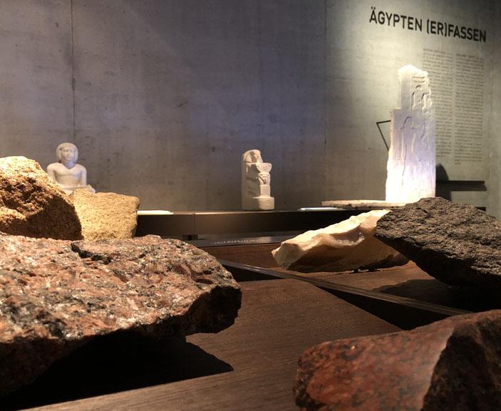 Raumansicht Ägypten Erfassen im Ägyptischen Museum München, Steine im Vordergrund, Skulpturen im Hintergrund. Selbsttest, Freiraum.