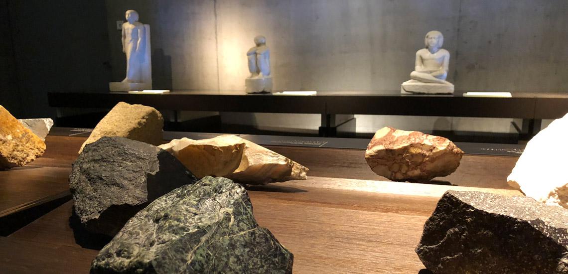 """Blick in Raum """"Ägypten (er)fassen"""" im Ägyptischen Museum München. Angeschnittene Steine im Vordergrund. Hinten beleuchtete Skulpturen. Selbsttest """"Blind Kunst sehen"""" von Tanja Praske für Freiraum"""