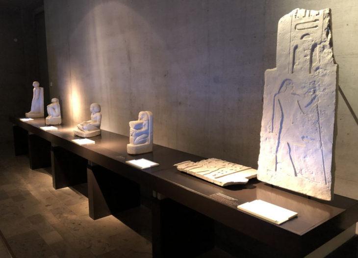 Raumansicht von Ägypten erfassen im Ägyptischen Museum München. Flachrelief und Statuen auf Tisch. Selbsttest im Ägyptischen Museum München, Freiraum.
