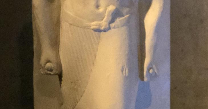 Detail von einer Stand-Schreitfigur im Ägyptischen Museum München. Zu sehen: Hände mit geballten Fäusten, darin ein Zepter, das die Figur als Lippi, Flötenspieler des Königs identifiziert. Selbsttet, Freiraum.t