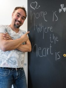 "Tom vor Tafel mit Schriftzug ""home is where the heart is"""