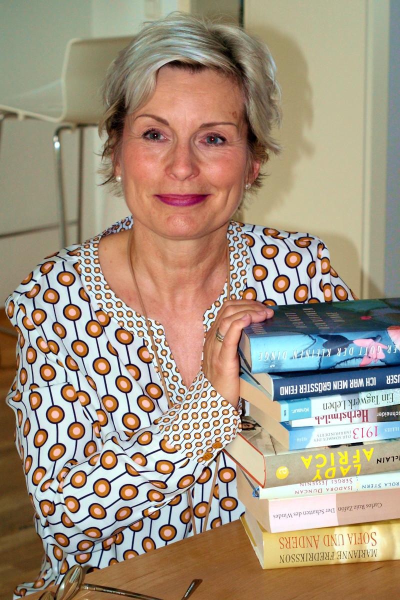 Franziska Feind sitzt vor einem Bücherstapel an einem Tisch. Sie trägt eine weiße Bluse mit braunen Punkten und lächelt in in die Kamera. Foto: Nina Jarosch
