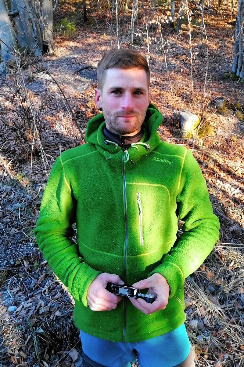 Jan-Marco Donat ist Baumpfeger. Er trägt eine grüne Fleece-Jacke und blaue Arbeitshosen und steht in einem Wald. In der Hand hält er einen Karabinerhaken, den er zum Klettern benötigt. Foto: Nina Jarosch