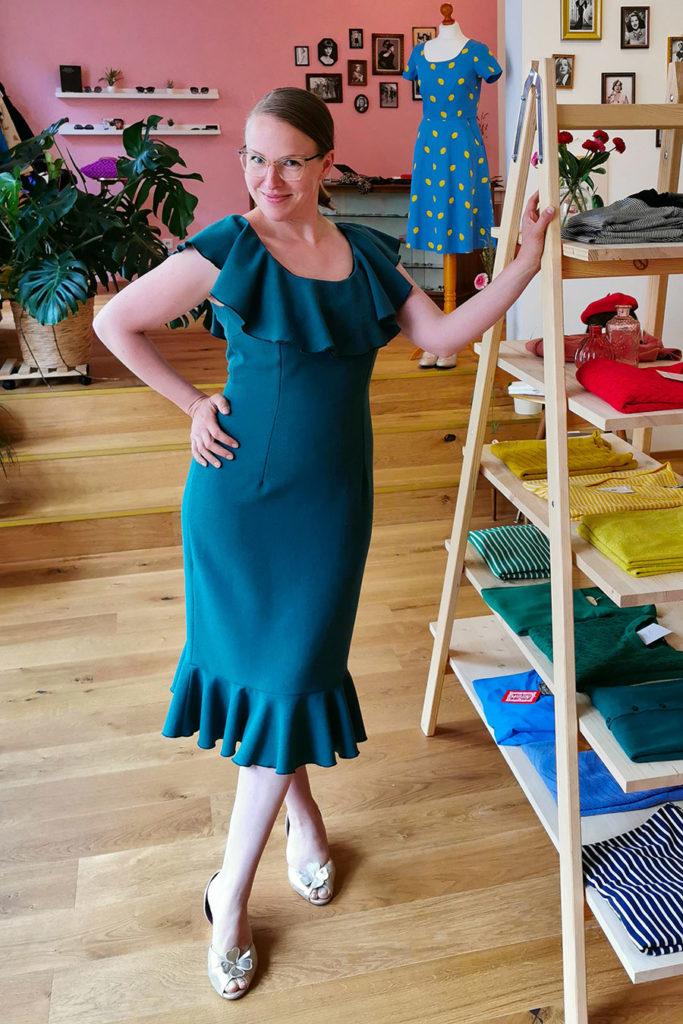 Ladenbesitzerin Johanna Hellmich steht lächelnd in ihrem Laden Schmachtfetzen und trägt ein grünes Kleid. Foto: Johanna Hellmich
