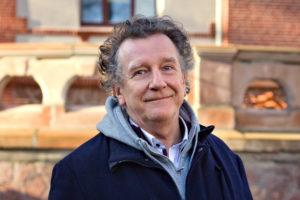 Vereins- und Genossenschaftsvorstand Roland Gebert steht vor der Terasse des Peißnitzhauses. Er trägt eine blaue Jacke und einen grauen Pulli über seinem Hemd und lächelt. Im Hintergrund scheint die Sonne auf den Sandstein und die Ziegelsteine des Kulthauses.