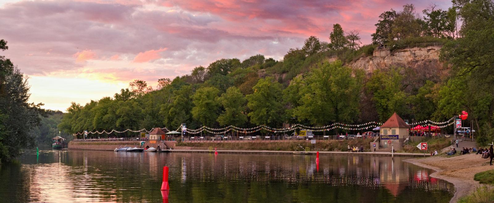 Blick von der Ziegelwiese des Peißnitzparks in Halle auf das Riveufer, ein befestigte Uferanlage aus Sand- und Backstein. Der rosafarbene Sonnenuntergang taucht den Fluss, die Bäume und die dahinterliegende Feldklippe in kitschiges Licht. Am Ufer sind Laternenreihen aufgehangen. Foto: Jonas Kessel