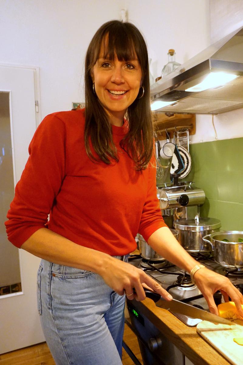 Judith Niemeyer lächelt in die Kamera, trägt einen roen Pullover und schneidet einen Kürbis in ihrer Küche. Foto: Nina Jarosch