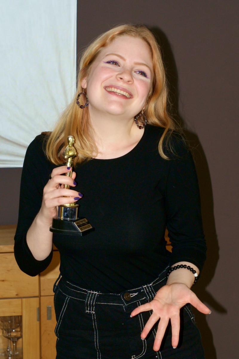 Lea Allinger trägt schwarze Kleidung, hält eine Oscar Statue in der Hand und lächelt ein imaginäres Publikum an. Foto: Nina Jarosch