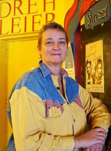 Hat trotz Corona-Krise gegründet: Die Geschäftsführerin der Drehleier Manuela Hoffmann trägt ein gelbes Jeanshemd und steht im Theater Drehleier an der Kasse. Foto: Nina Jarosch