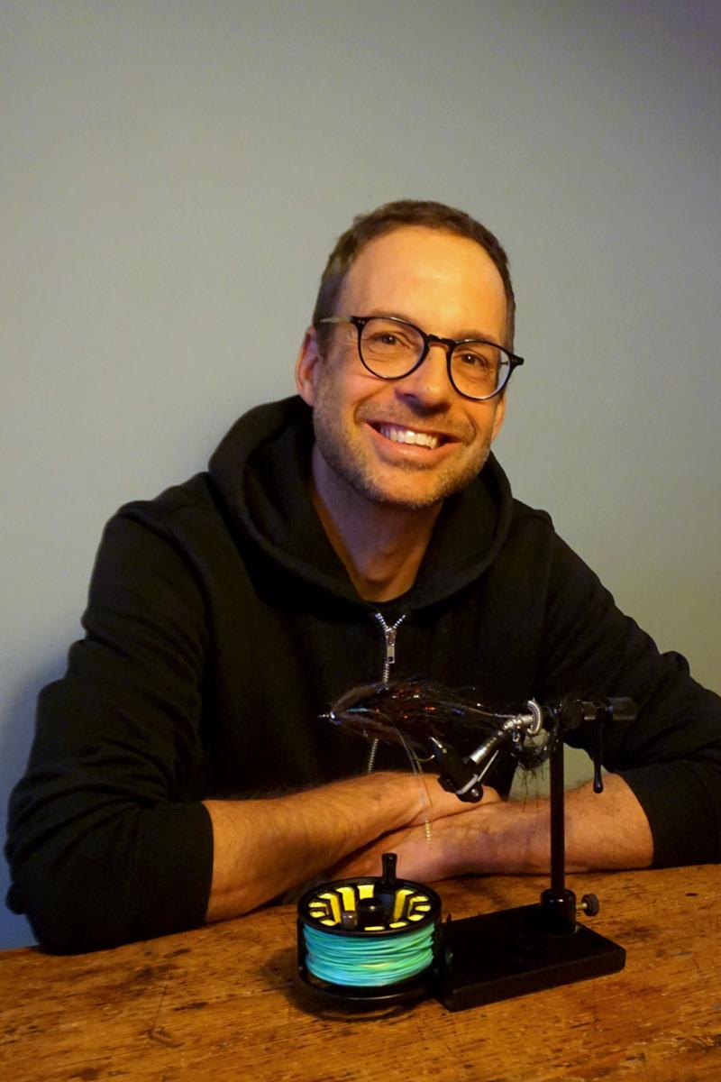 Oliver Landgraf sitzt an einem Tisch und trägt eine Brille und einen schwarzen Hoodie. Vor ihm liegt auf dem Tisch eine Fliegenrolle aus dem Angelsport und ein Fliegen-Bindestock. Foto: Nina Jarosch