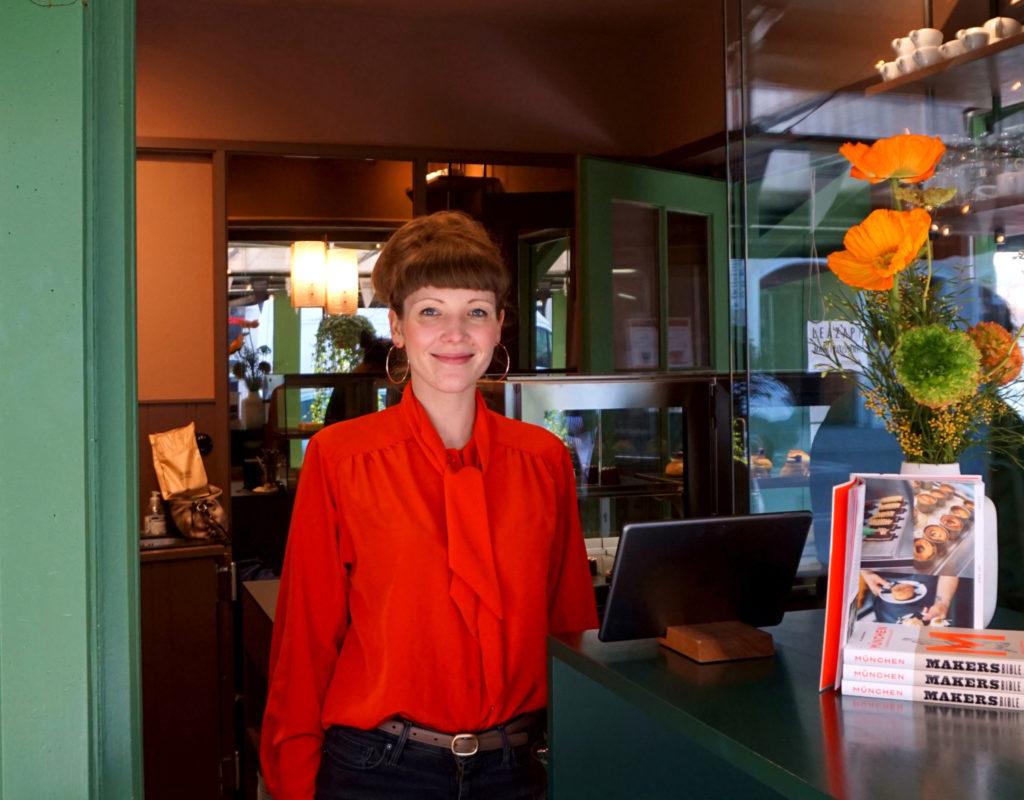 Mit Mut und Herzblut durch die Krise: Lea Zapf trägt eine rote Bluse und steht an dem Ausgabefenster ihres Stands Marktpatisserie. Foto: Nina Jarosch