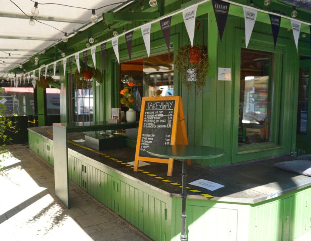 Der Stand Marktpatisserie ist grün gestrichen und mit Wimpelgirlanden ud Pflanzengeschmückt. Foto: Nina Jarosch