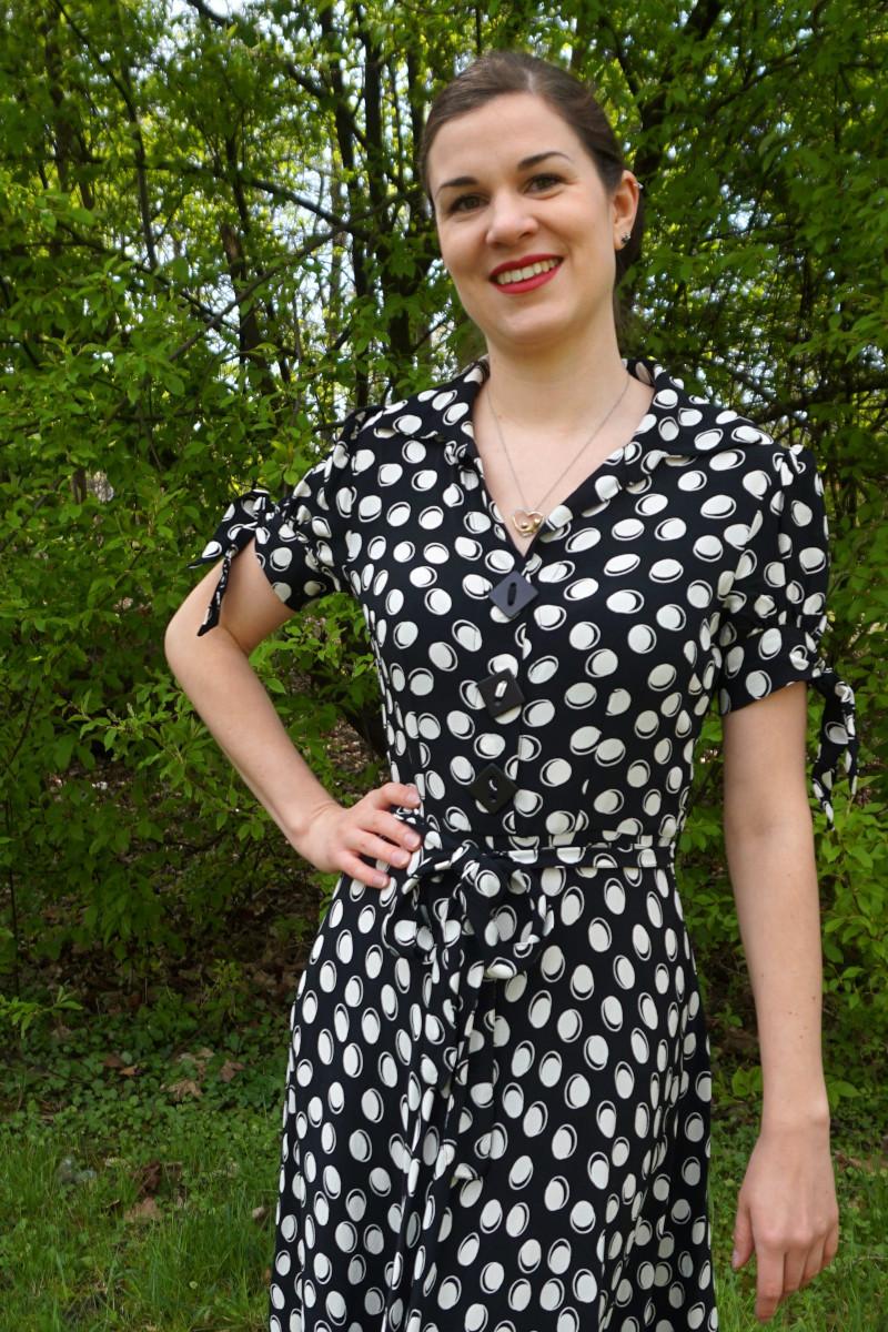 Sandra Brand trägt ein schwarzes Kleid mit weißen Punkten im Vintage-Stil. Sie stützt eine Hand in die taille und lächelt adrett in die Kamera. Sie steht in einem Park. Foto: Nina Jarosch