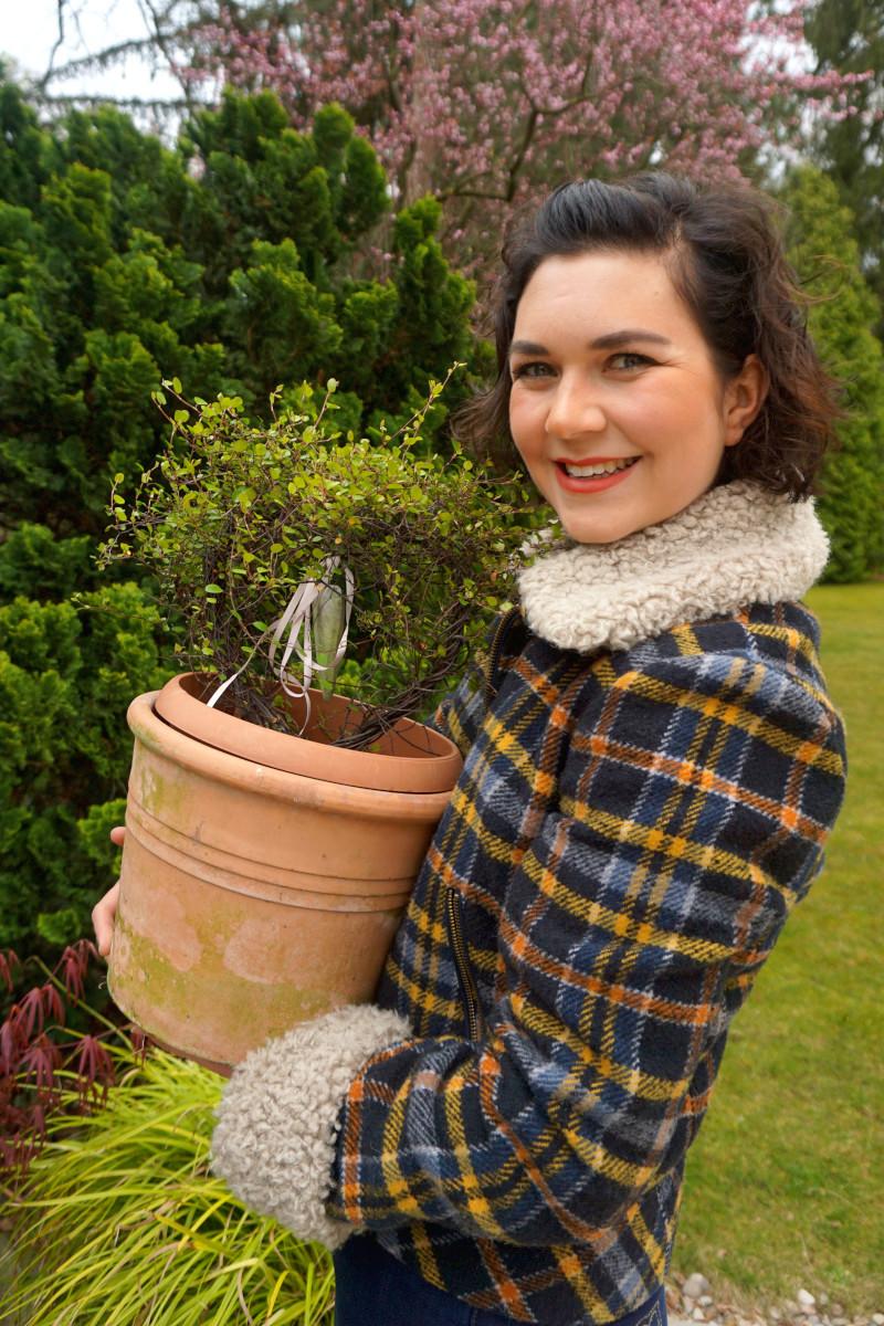 Victoria Stettnersteht im Garten und trägt eine karierte Winterjacke, lächelt in die Kamera und hat einen Blumentopf in den Händen. Foto: Nina Jarosch