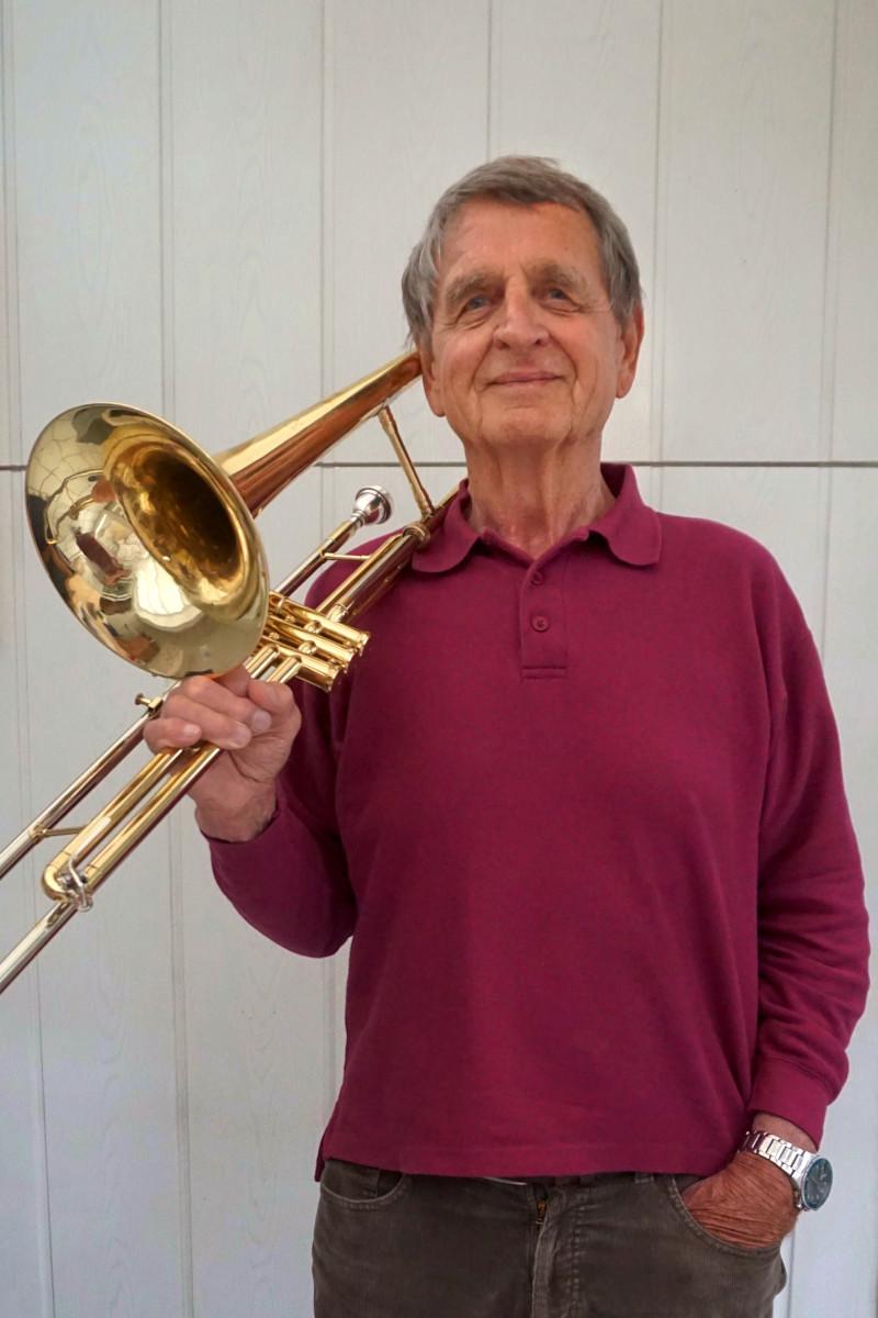 Werner Riedel trägt einen violetten Pullover und hat lässg sein Instrument die Tenorpsaune geschultert. Foto: Nina Jarosch