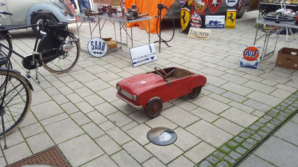 Rotes Oldtimer-Spielzeugauto steht auf dem gepflasterten Austellungsgelaende in Fuerstenfeld