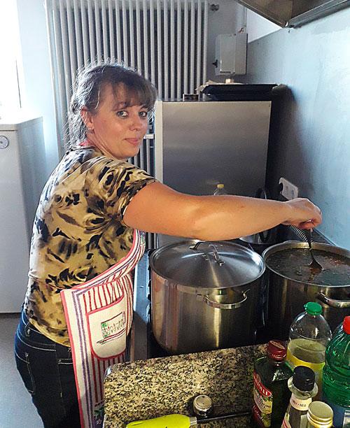 Frau in Küche vor Suppentopf