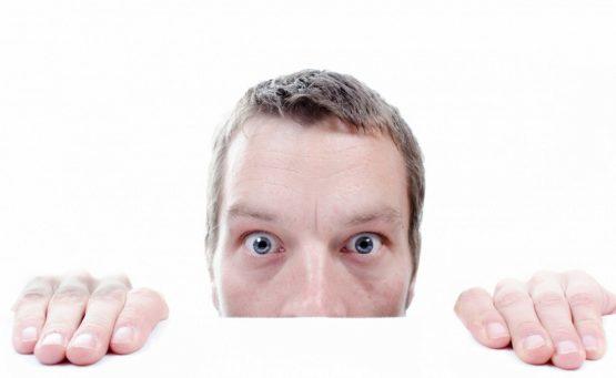Mann mit blauen Augen und Händen über Tischplatte schaut erstaunt