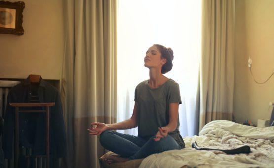 Frau meditiert auf Bett