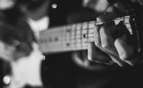 schwarzweiss Foto von Händen die eine e-Gitarre spielen
