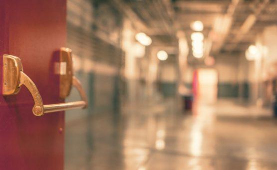 Rote geöffnete Krankenhaustüre mit Blick in eine unscharf fotografierte Station