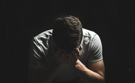 Mann sitzt mit Händen vor Augen in Verzweiflung vor dunklem Hintergrund