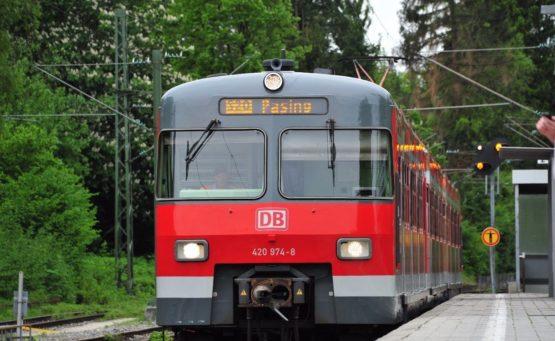 Roter Zug Baureihe 420 steht an einer Bahnhaltestelle im Hintergrund grüne Bäume
