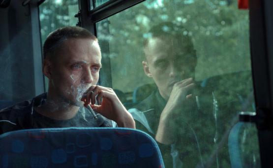 Ein junger Man sitzt im Bus und raucht, sein Gesicht spiegelt sich im Busfenster. Bild aus dem Film