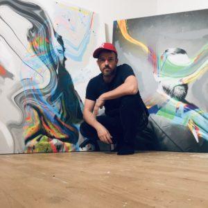 Foto von René Arbeithuber vor zwei seiner Bilder