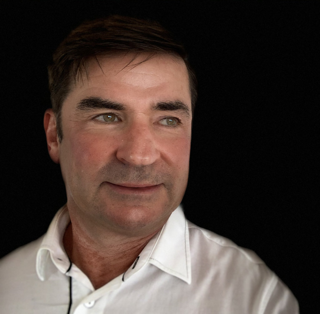 Portraifoto von Roland Strobl vor schwarzem Hintergrund. Er trägt ein weißes Hemd und blickt nach links