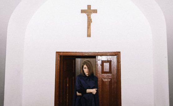 Eine Frau steht in der Tür einer Kirche über der Tür hängt Jesus-Kreuz