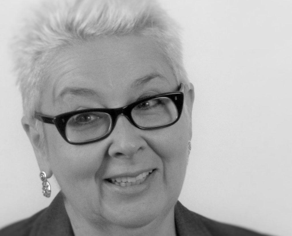 Blonde, kurzhaarige Frau mit markanter dunkler Brille hält den Kopf leicht nach links geneigt und lächelt leicht