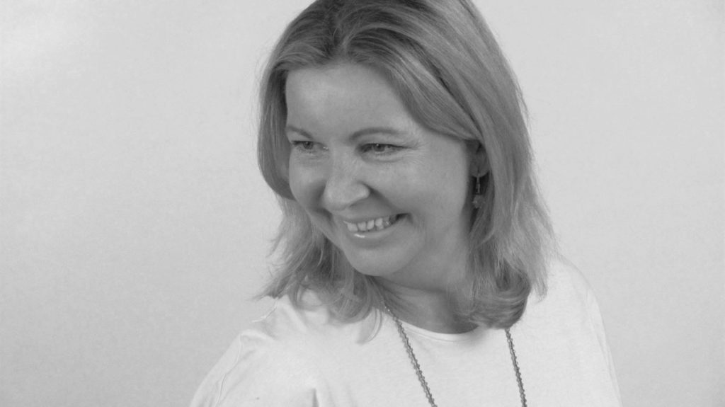 Elke_Böhm_Porträt_blonde Frau mit schulterlangem Haar und weiße Bluse lächelt nach links unten
