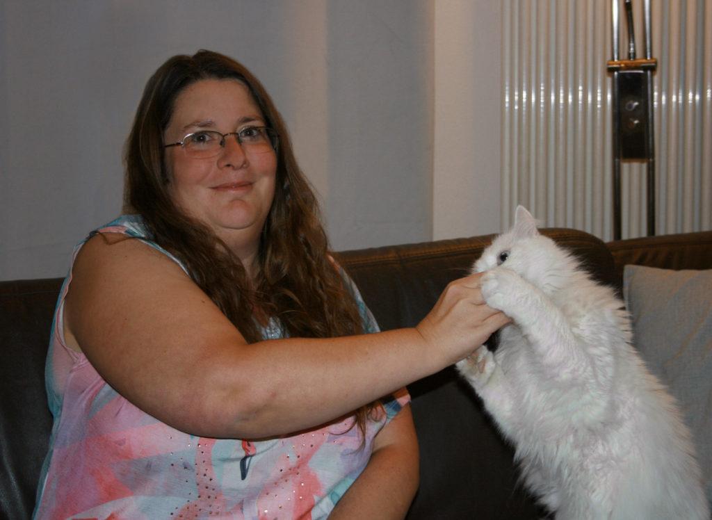 """Katzenpsychologin Anja Mürner sitzt auf einer Couch, neben ihr Katzer """"Chewbacca""""."""