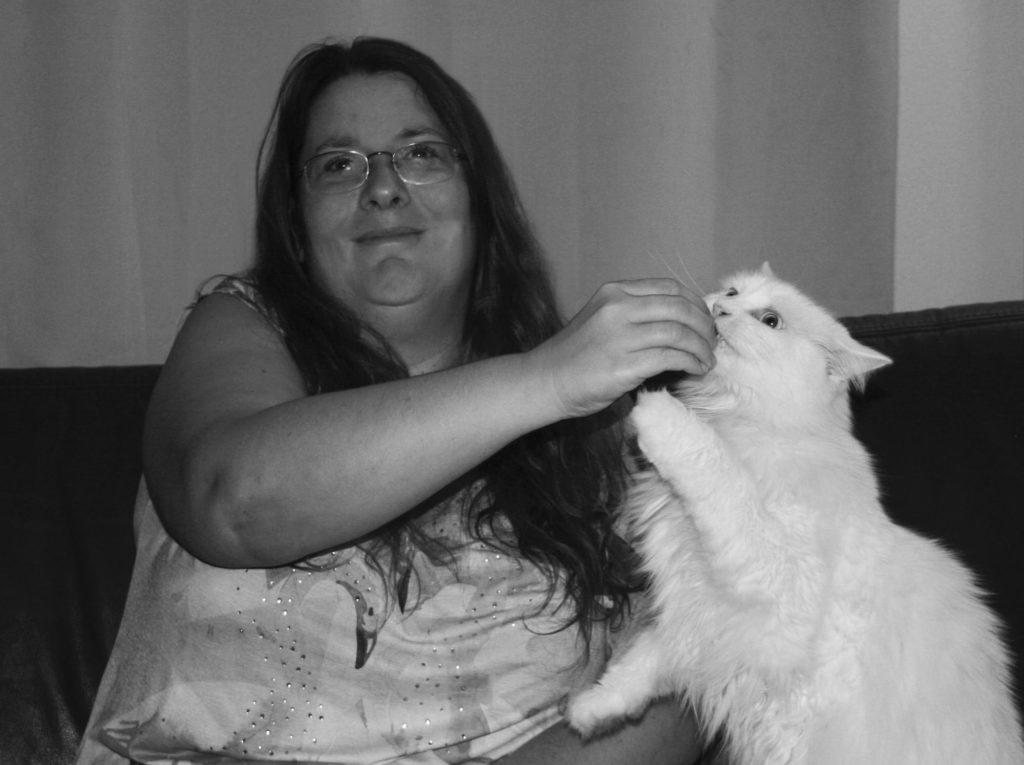 """Katzenpsychologin Andrea Mürner lächelt in die Kamera und füttert Kater """"Chewbacca"""", der Männchen macht, mit einem Leckerli."""