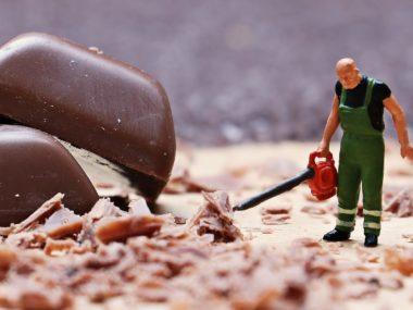 Eine Miniaturfigur mit Arbeitsmontur und Laubbläser bläst Schokospäne auf Schogettenstücke zu