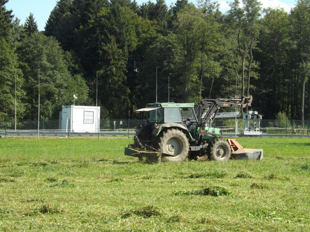 Ein Traktor mit Kreiselmäher fährt auf einer Wiese vor einer eingezäunten Meßstation für Klimaforschung im oberbayerischer Weiler Fendt