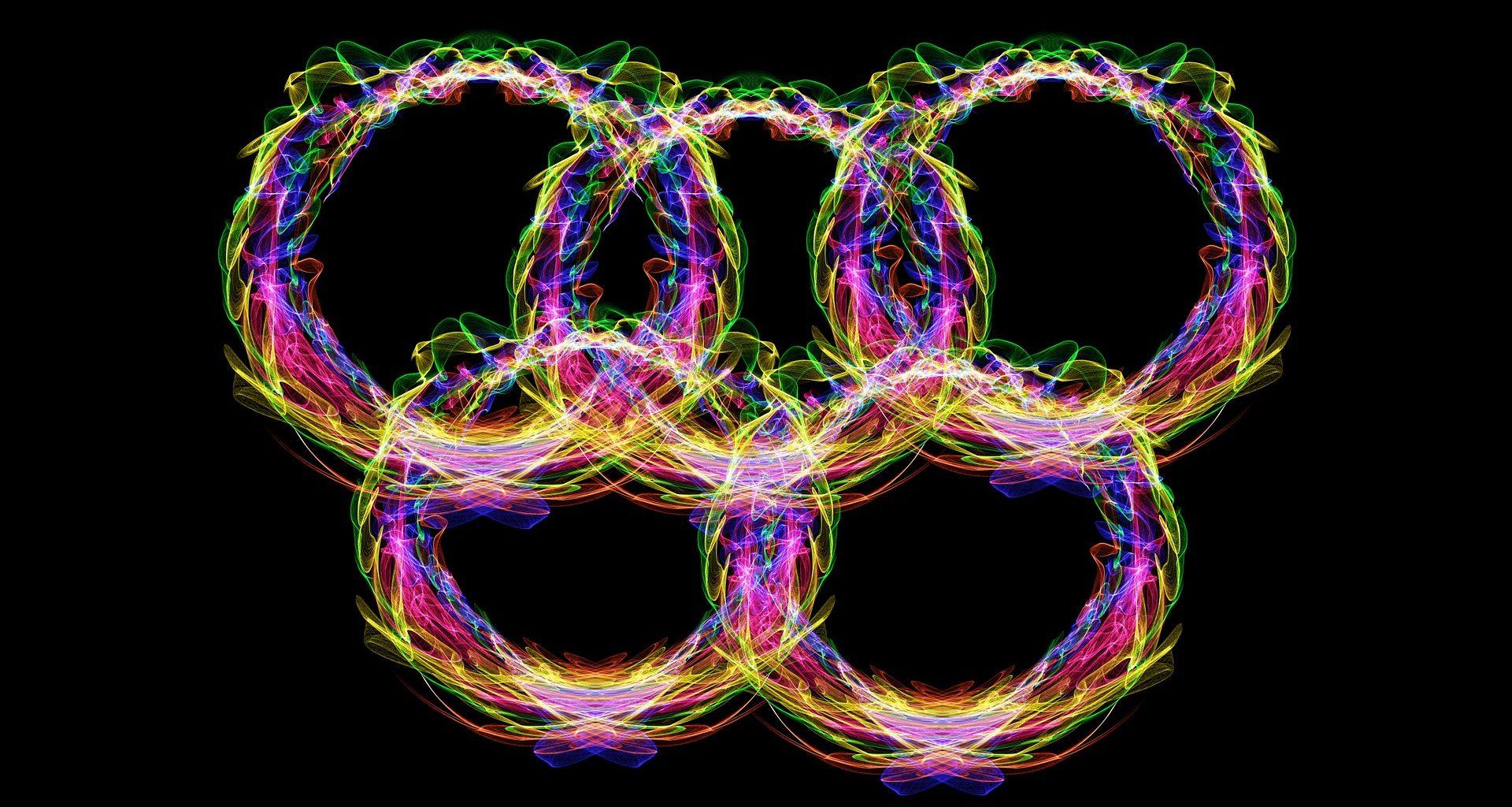 Fünf Olympiaringe aus buntem Neonlicht vor schwarzem Hintergrund
